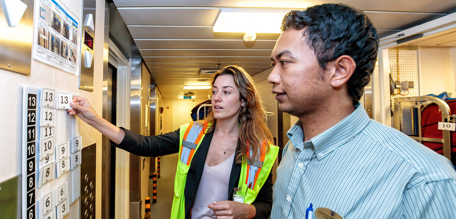 10:43 am – Porsche consultant Renate Fuchs discusses luggage distribution with a member of the crew. A numbering system is used to deliver batches of luggage evenly via elevators throughout the 16 decks. This prevents obstructions in the halls. Photo: Porsche Consulting.